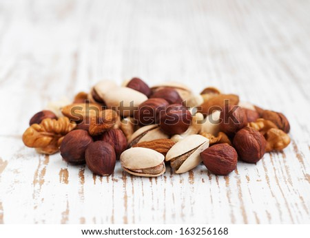 Mixed nuts on a old wooden background - stock photo