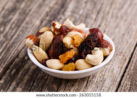Mixed nuts on a plate on wooden background. - stock photo