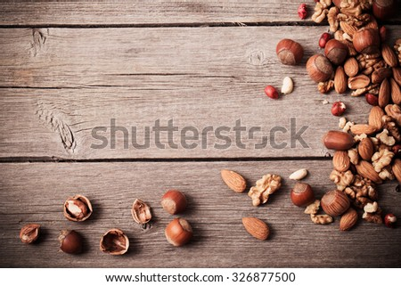 Mixed nuts on old wooden background - stock photo