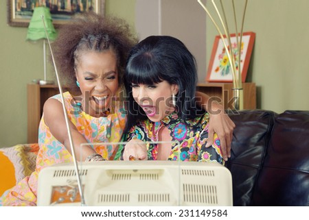 Mixed pair of friends laughing together in front of television - stock photo