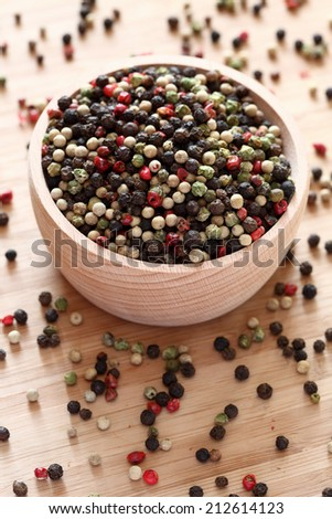 Mixed peppercorns in a wooden bowl. Close-up.