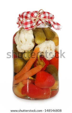 Mixed pickled vegetables in glass jar - stock photo