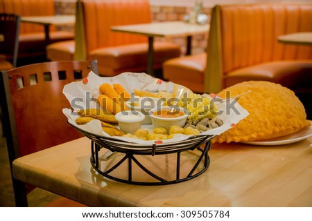 Mixed platter beautifully arranged with mix of typical latin foods such as empanadas, corn, abbas, salsas on table and large empanada next to basket. - stock photo