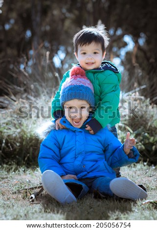 Mixed race Asian Caucasian brothers playing in the park on a cold winter morning wearing green and blue winter jackets - stock photo