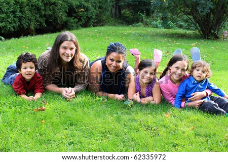 Mixed race beautiful ethnic family with parents and four children laying on the grass - stock photo