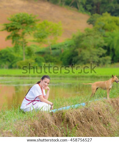 mixed-race beautiful karen girl sit on rice field lookforward with dog