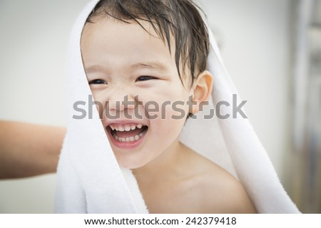 Mixed Race Boy Having Fun at the Water Park with White Towel On His Head. - stock photo