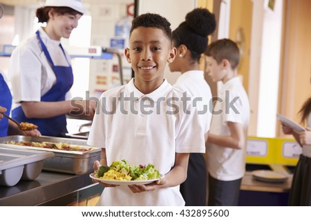 Mixed race boy holding a plate of food in a school cafeteria - stock photo