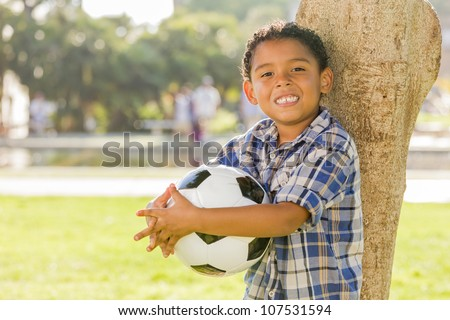 Mixed Race Boy Holding Soccer Ball in the Park Against a Tree. - stock photo