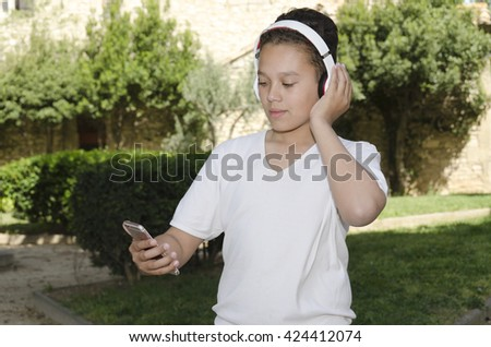 mixed race boy listening to music with his smart phone and headphones