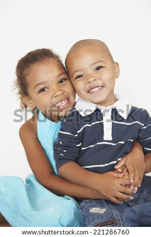 Mixed Race brother and sister hugging - stock photo
