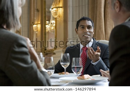 Mixed race businessman in discussion with colleagues at restaurant table - stock photo