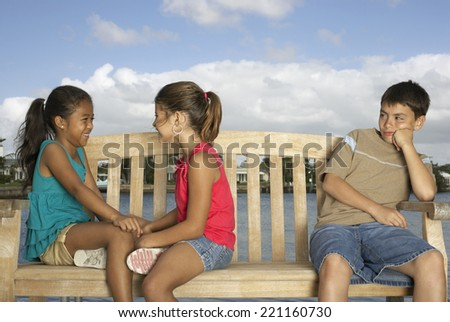Mixed Race children on bench - stock photo