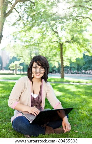 Mixed race college student sitting on the grass working on laptop at campus