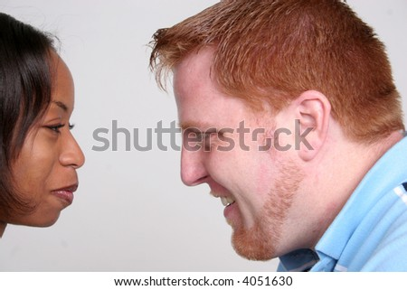 Mixed race couple smiling at each other
