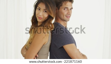 Mixed race couple standing back to back - stock photo
