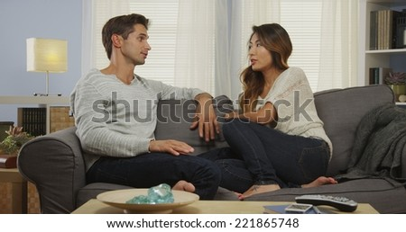 Mixed race couple talking on couch