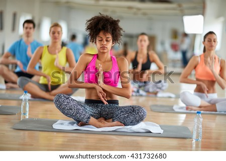 Mixed race curly female meditate in group and relaxing in lotus pose indoor - stock photo