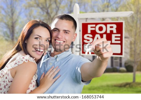 Mixed Race Excited Military Couple In Front of New Home with New House Keys and For Sale Real Estate Sign Outside.