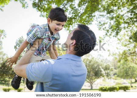 Mixed Race Father and Son Playing Together in the Park. - stock photo