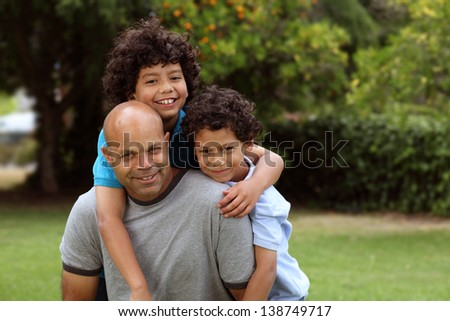 Mixed race father and sons playing outside