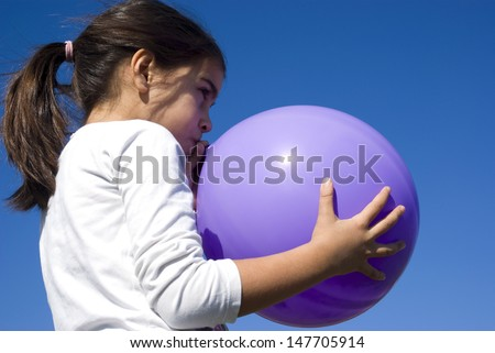 Mixed race girl blowing up balloon - stock photo