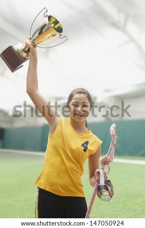 Mixed race girl lacrosse player holding trophy - stock photo