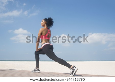 Mixed race girl stretching on beach