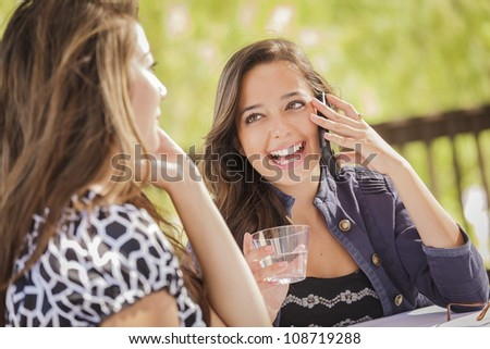 Mixed Race Girls Talking on Their Mobile Cell Phones Sitting Outside at a Table. - stock photo