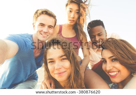 Mixed race group of friends walking in Santa monica beach and taking selfies - stock photo