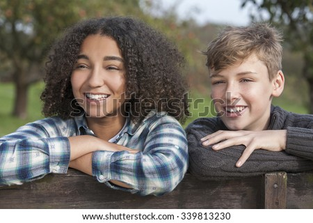 Mixed race group of two happy children teenagers, African American girl caucasian boy leaning on fence laughing together in the countryside - stock photo