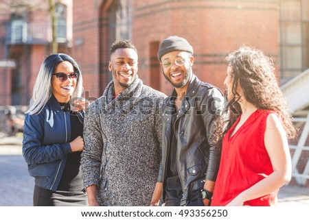 Mixed race group portrait in Hamburg, Germany. Four persons, with different ethnicities and wearing urban style clothes, looking each other and smiling. Lifestyle and friendship concepts.