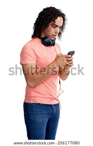 Mixed race guy with his headphones looking at his cellphone in studio