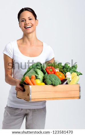 Mixed race happy young woman holding a crate full of fresh organic vegetables on grey background, promoting healthy diet and lifestyle - stock photo