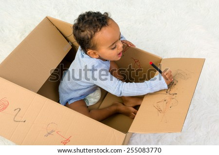 Mixed race little toddler boy sitting in a cardboard box playing with crayons - stock photo