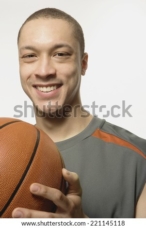 Mixed Race man holding basketball - stock photo