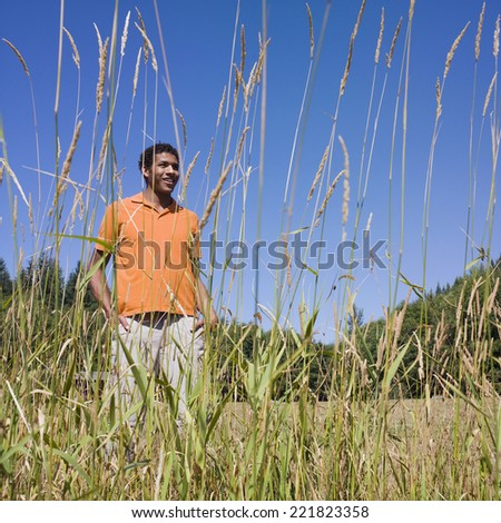 Mixed Race man in tall grass - stock photo