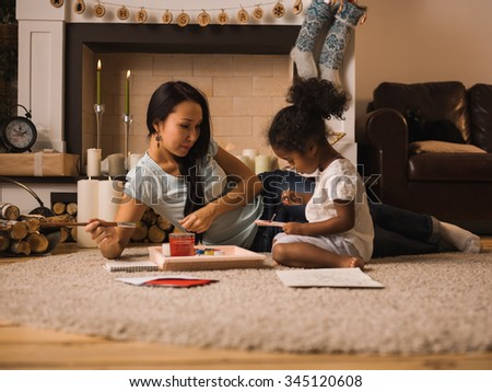 Mixed race mother and daughter playing and painting near Christmas tree at home - stock photo