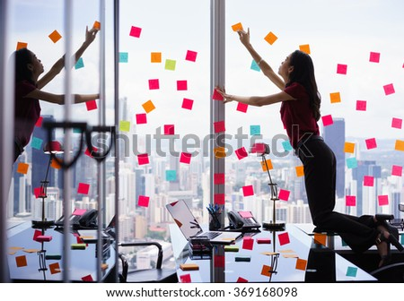 Mixed race secretary working in modern office in skyscraper, sticking adhesive notes with tasks on window. The girl feels stressed and overwhelmed - stock photo
