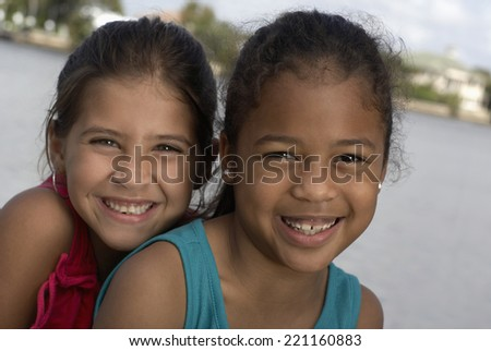 Mixed Race sisters in front of water