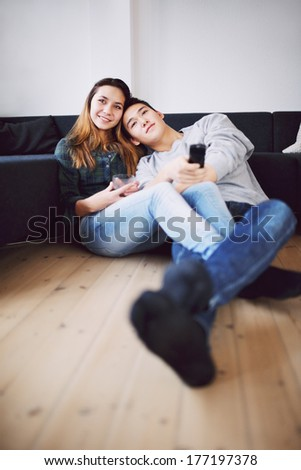 Mixed race teenage guy holding remote control relaxing with his beautiful girlfriend at home. Loving young couple sitting together on floor watching TV. - stock photo