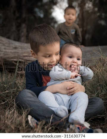 Mixed race Thai Asian Caucasian brothers (4 months, 2 years, and 5 years) play together outside in nature. Desaturated color effects. - stock photo