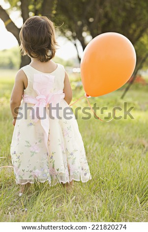 Mixed race toddler holding balloon - stock photo