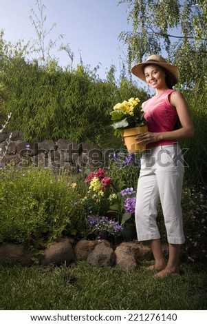 Mixed Race woman holding potted plant - stock photo