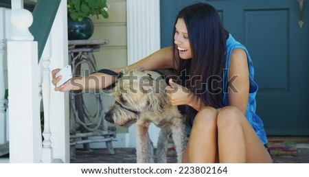 Mixed race woman sitting on porch taking pictures with dog
