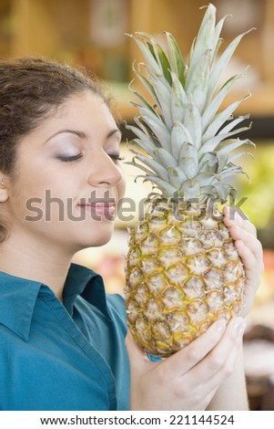 Mixed Race woman smelling pineapple - stock photo