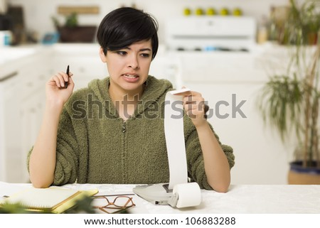 Mixed Race Young Female Agonizing Over Financial Calculations in Her Kitchen. - stock photo