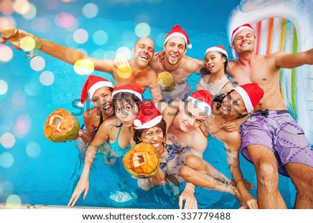 mixed raced  group of nine people celebrating christmas in a swimming pool (focus on frontal row of people) - stock photo