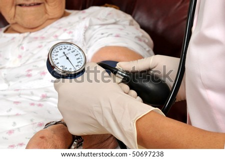 Mixed raced nurse measuring senior patient's blood pressure - series of MEDICAL IMAGES. - stock photo
