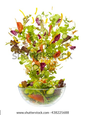mixed salad jumping and flying from the glass bowl - stock photo